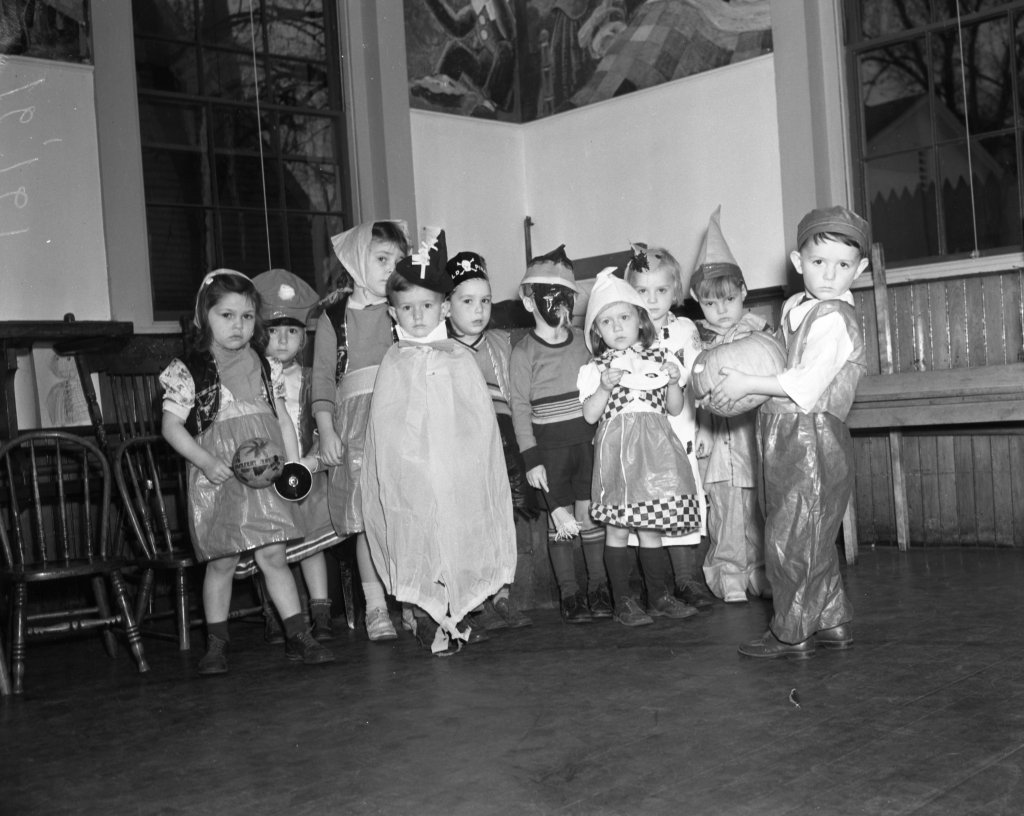 """Oct. 31, 1939 Evening Express. Uncredited. Original caption: """"Bobby Doherty of Monument Street Kindergarten holds his Jack O-Lantern for all to see. The other masqueraders, at the same school, are Carol Thurman, Elaine Silverman, Jean Black, Billy Gilman, Beatrice Wilson, Ronnie Brett, Dorothy Sullivan, Cecil Wheeler and Betty Ann Peterson."""""""