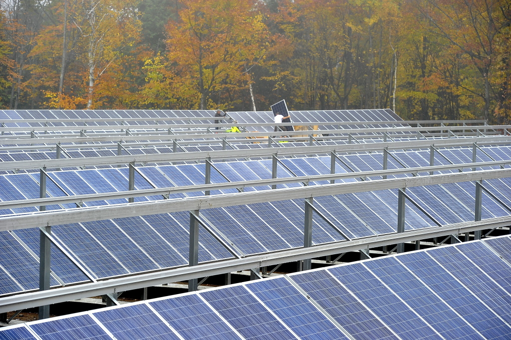 Workers and master electricians install solar electric panels in part of the parking lot at the Mout Abram ski area in Greenwood.