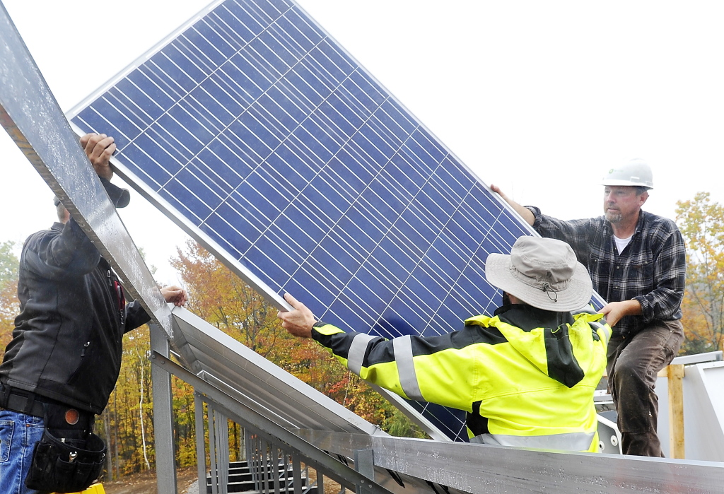(FILE) Electricians install a solar electric panel into an 800-panel array at Mt. Abram Ski Area in October 2014.