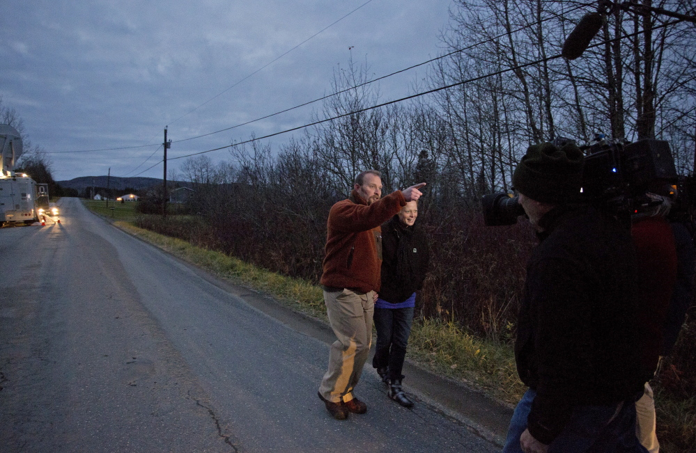 Ted Wilbur points back to his house on Violette Settlement Road in Fort Kent after taking a walk with his girlfriend, Kaci Hickox, on Friday, after a judge ruled against the state's petition seeking restrictions on her movement.