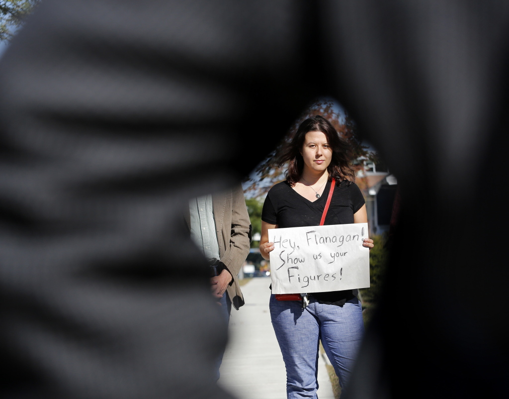 Adrianne Hess of Portland holds a sign aimed at USM President David Flanagan during a press conference after Monday's announcement of faculty layoffs.