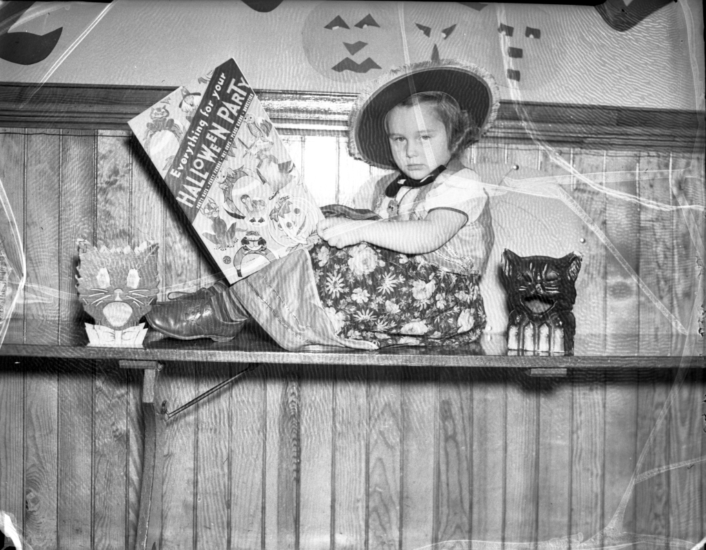 """Uncredited photo from the Oct. 27, 1937 Evening Express.  Original caption: """"Elaine Stevens [of the Longfellow School sub-primary class], just a bit perplexed with all the many Halloween suggestions, decides to study a book on the matter of 'giving a party.'"""""""