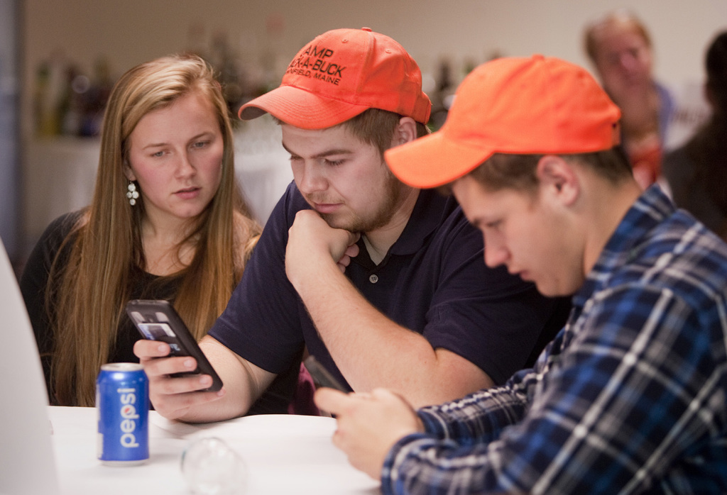 No on 1 bear supporters Brianna Pelkie of Fryeburg, Walker Day of Lovell and Caleb Winslow of Parsonsfield check the returns on their phones during an election night gathering at the Black Bear Inn in Orono.