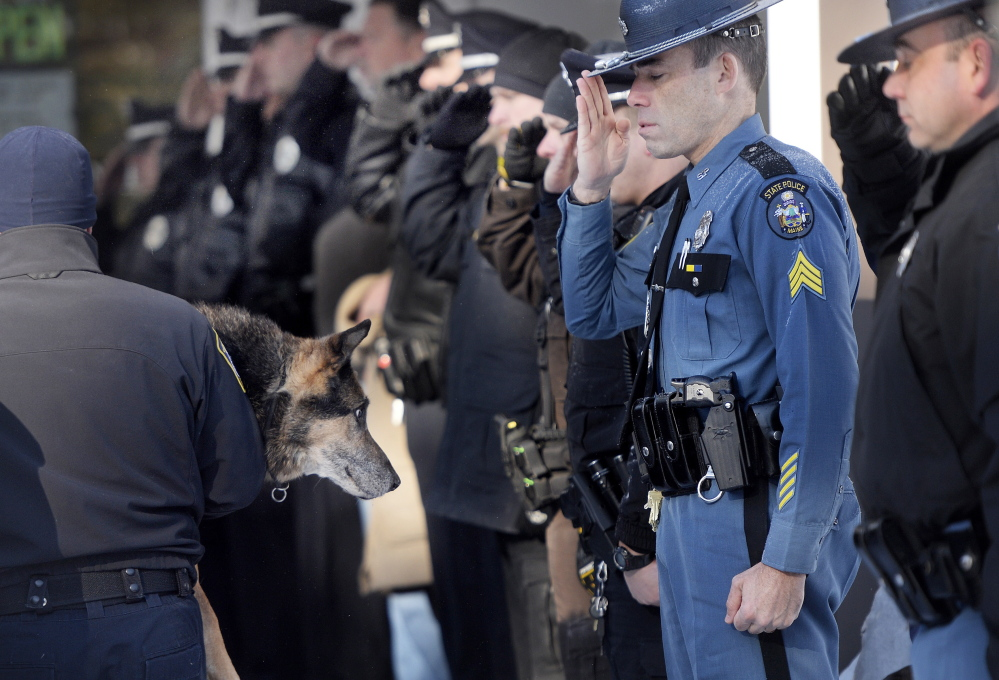 Sgt. Robert Burke of the Maine State Police salutes along with other officers as South Portland Police Officer Shane Stephenson carries Sultan, a retired Yarmouth police dog, into the Yarmouth Veterinary Center, where he was euthanized Friday.