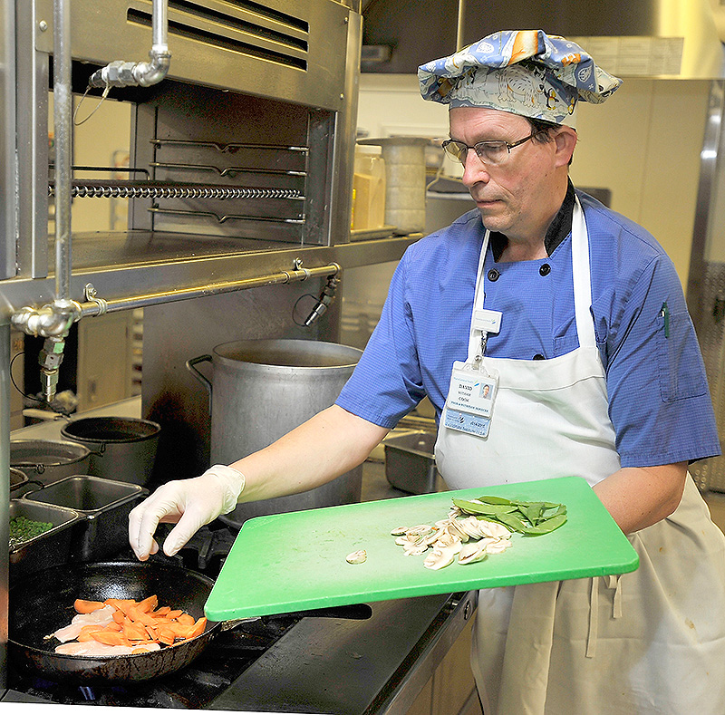 David Witham, a cook at the Maine General Medical Center in Augusta, prepares a chicken and vegetable stir-fry with locally grown carrots. The dish is one of several healthier options that can be ordered by patients at the hospital.