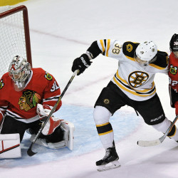 Chicago Blackhawks goalie Antti Raanta (31) makes a save against Boston Bruins' Jordan Caron (38) while Blackhawks' Michal Rozsival (32), of The Czech Republic, looks on during the second period of an NHL hockey game Sunday. The Associated Press