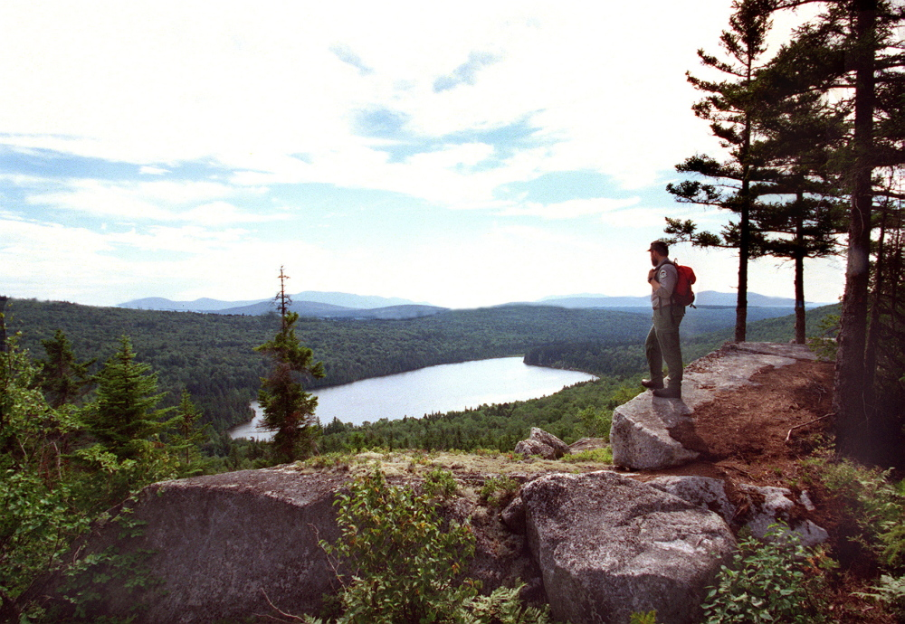 """A Maine forester overlooks Sing Sing Pond along the Turtle Ridge Trail in the Nahmakanta Lake region between Moosehead Lake and Baxter State Park. Under Gov. Paul LePage's proposed timber-harvesting changes for state-owned forestlands, such as the 44,000 acres that make up Nahmakanta Public Reserved Lands, critics fear a dramatic shift in the multiple-use philosophy that has guided management for decades. LePage officials insist the """"underlying, guiding"""" principles regarding harvesting on public land won't change."""