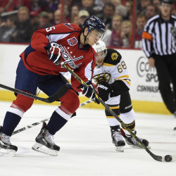 Washington Capitals left wing Andre Burakovsky carries the puck against Bruins right wing David Pastrnak during the first period of Wednesday night's game in Washington. The Capitals shut out the Bruins, 3-0.