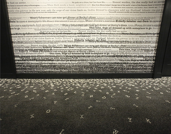 The walls of the guest room hallways at The Press Hotel contain actual headlines used in the Portland Press Herald over the years, as shown in this May 4, 2015 photograph of the newly-renovated hotel. Lower on the walls, the headlines compress and overlap lower and the rug has letters embedded in it, making it appear that the letters have fallen off the headlines on the wall. Developer Jim Brady has branded the history of the Portland Press Herald and newspaper journalism throughout the hotel, which is housed in the former Press Herald building.