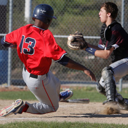 Thomas Wood of Gray-New Gloucester slides into home plate as the ball glances off the glove of Freeport's Caiden Shea.