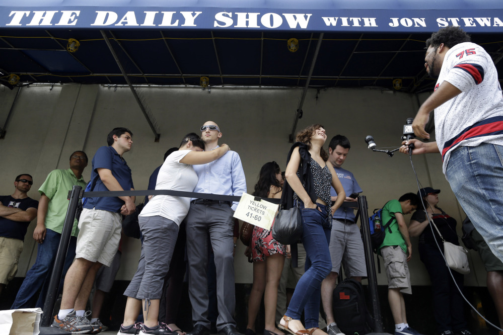 """Alexandra Mele, second from right, is interviewed and Ariana and Isaac Levin embrace as they wait in line to enter for the final taping of  """"The Daily Show with Jon Stewart"""" on Thursday in New York. Stewart said goodbye Thursday after 16 years on the show that established him as America's foremost satirist of politicians and the media."""