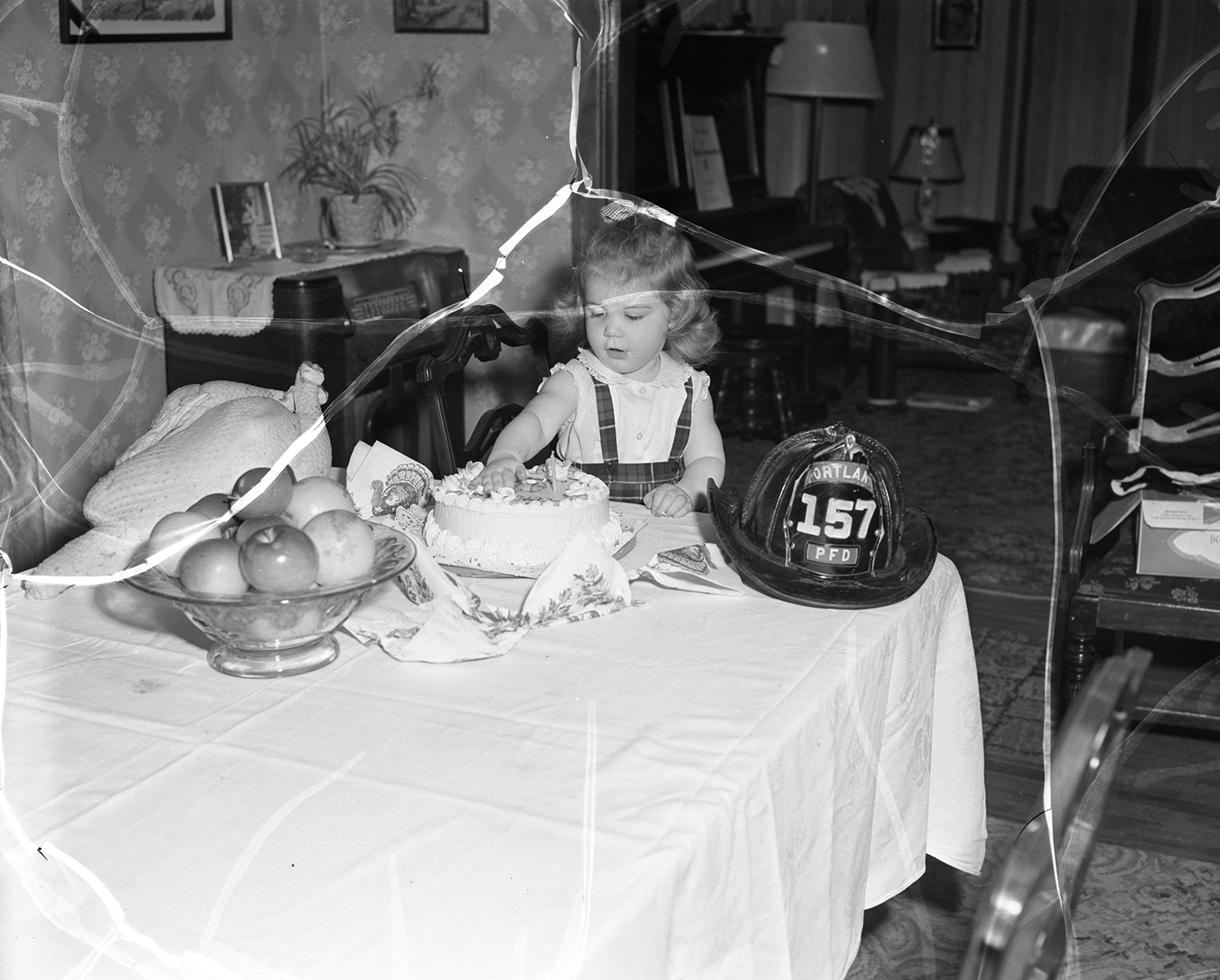 Little girl sits at the Thanksgiving table, with Portland Fire Department helmet, 1953. From the Portland Public Library archival collection of Portland Press Herald, Maine Sunday Telegram and Evening Express photos.