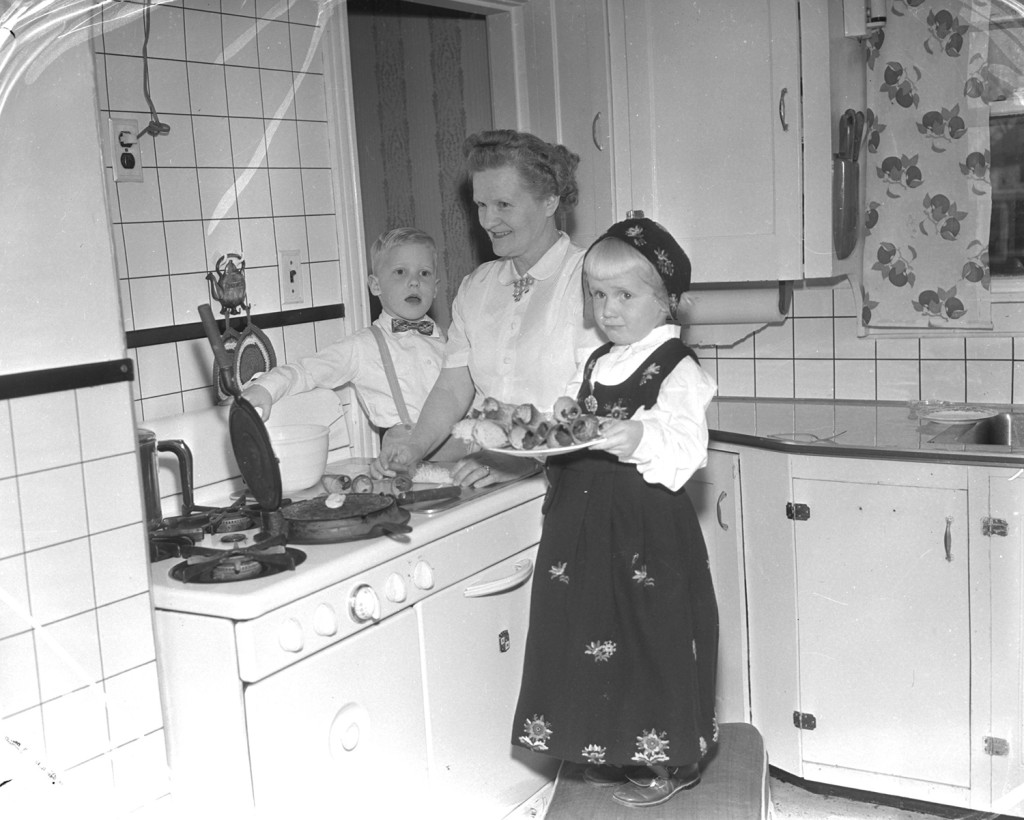 Mother and children making vaffleren (Norwegian waffles, 1954. From the Portland Public Library archival collection of Portland Press Herald, Maine Sunday Telegram and Evening Express photos.