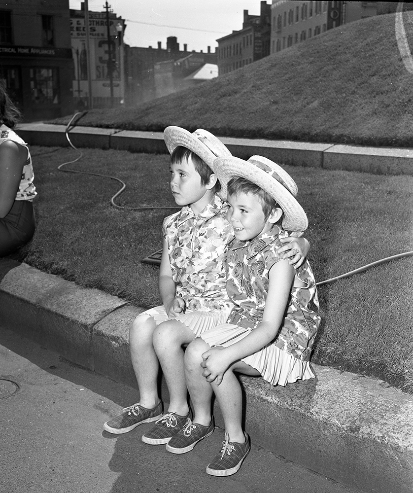 Two girls watch the Fourth of July parade in Portland, 1958. From the Portland Public Library archival collection of Portland Press Herald, Maine Sunday Telegram and Evening Express photos.