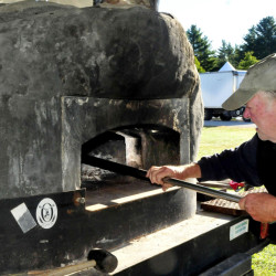 Vince Collins of Harvest Moon Pizza prepares to light a wood-fired oven while getting ready in the food court area of the Common Ground Country Fair site in Unity on Wednesday. The 39th annual fair begins Friday.