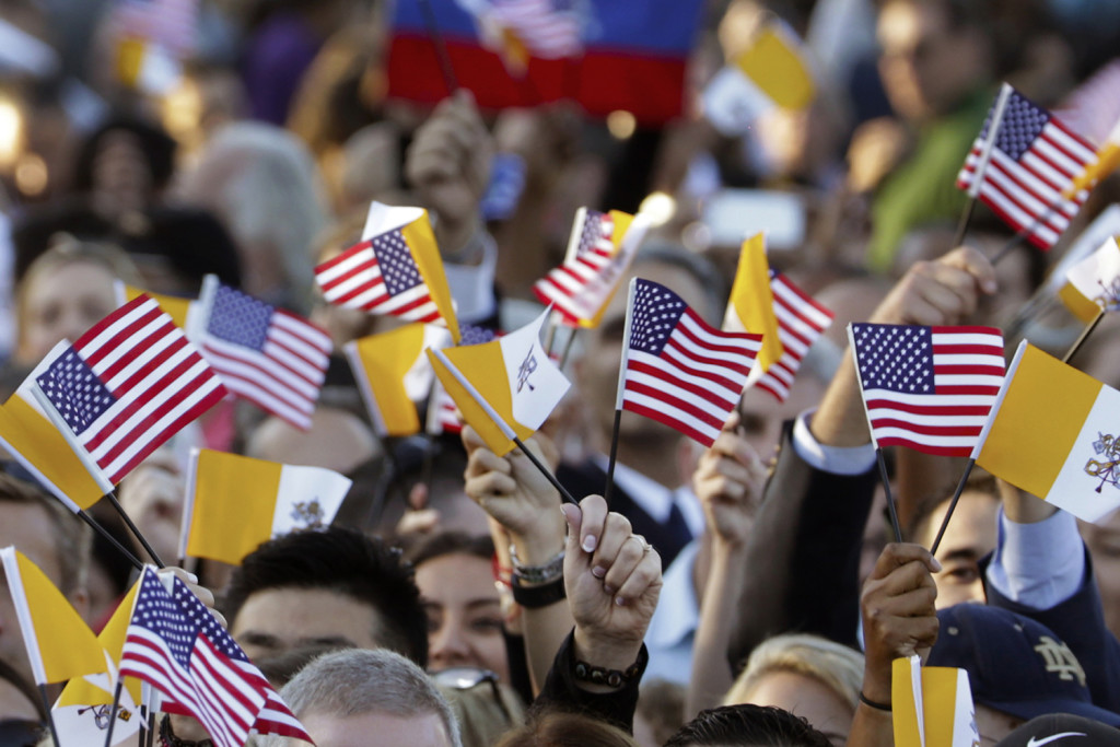 Spectators hoping for a glimpse of Pope Francis waves Papal and U.S. Flags on the South Lawn of the White House in Washington, Wednesday, before the official state arrival ceremony where President Barack Obama will welcome the pope. The Associated Press