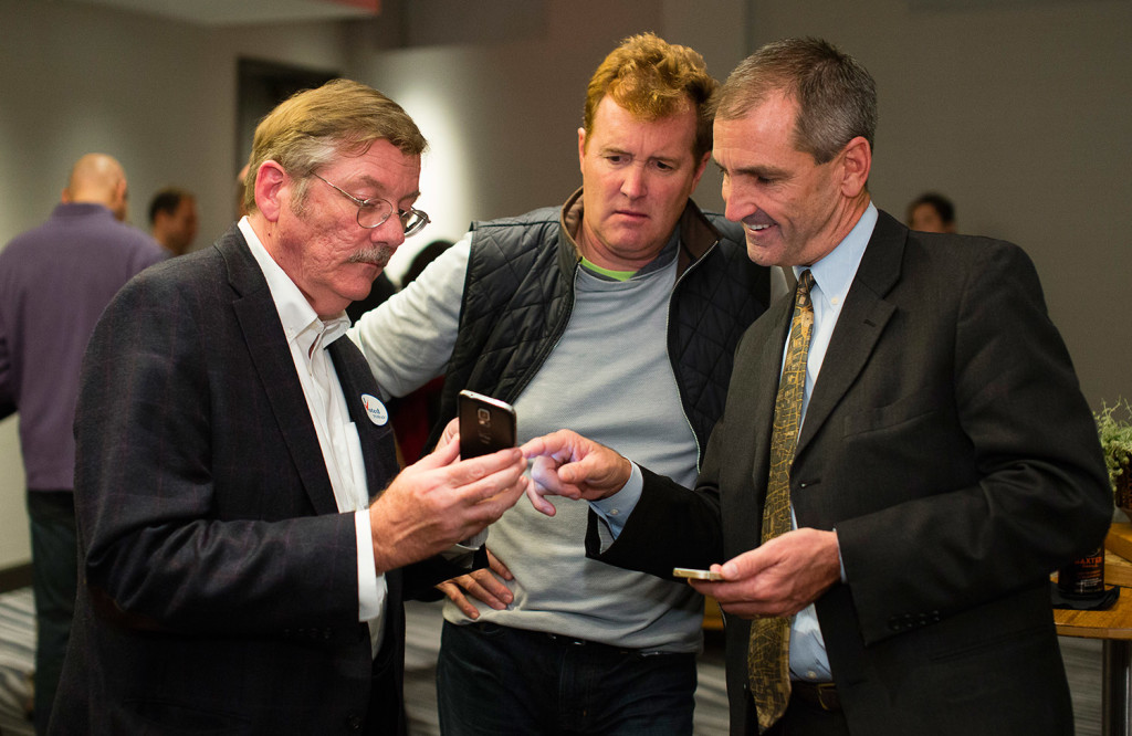 Portland Regional Chamber CEO Chris Hall, Portland Chamber of Commerce Executive Board Member Chip Harris, and Portland Community Chamber Liason to City Hall Chris O'Neil, check election results during a post election gathering for No on 1 campaign.