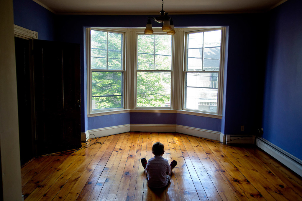 Graham Lovell sits on the floor or his family's new West End apartment after the family spent a month in a motel room.