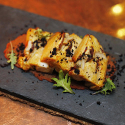 Octopus and chorizo strata with chorizo-onion puree and black olive pepper.