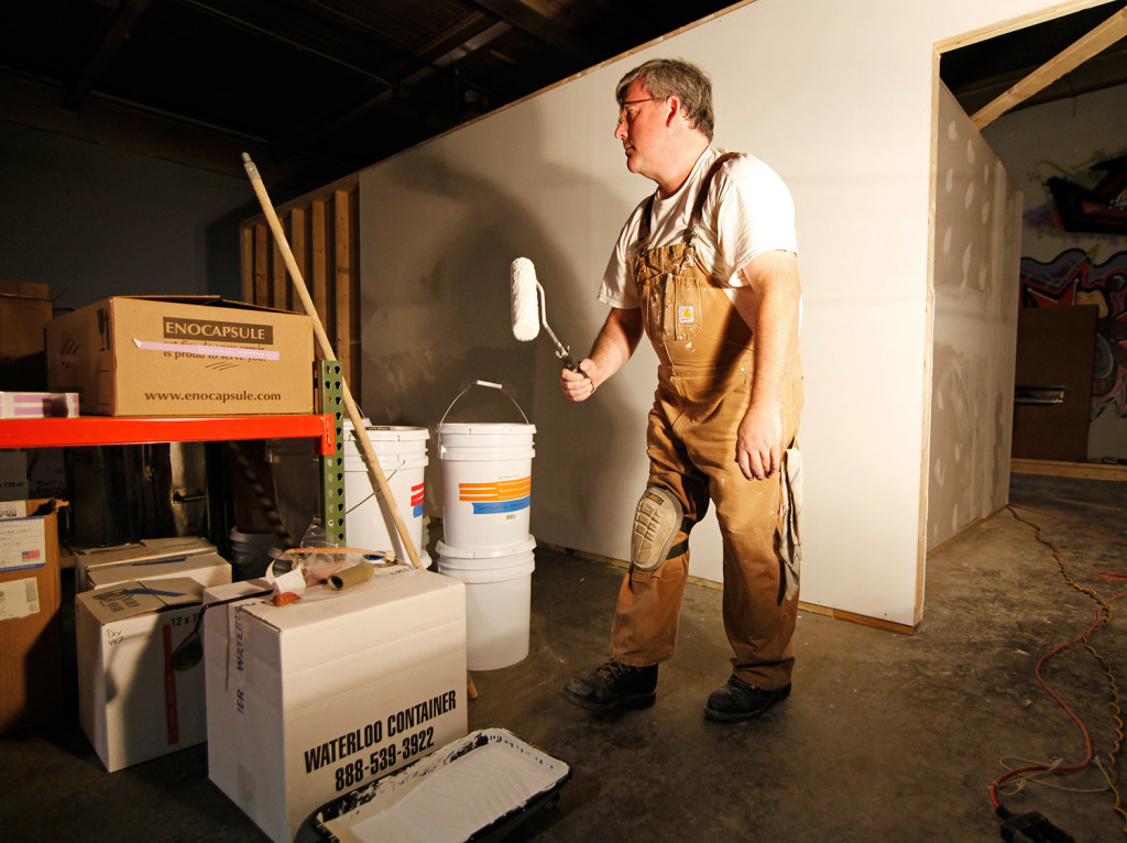 Phil Gaven, owner of the Honey Exchange, puts a layer of primer on the new space he is leasing for bottling honey and housing beekeeping materials at Maine Mead Works on Washington Avenue.