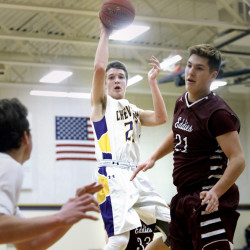 Jack Casale of Cheverus finds a teammate under the basket as Grant Hartley of Edward Little looks to defend during a boys' basketball game in Portland Friday night. Casale led the Stags with 16 points in a 52-40 victory.