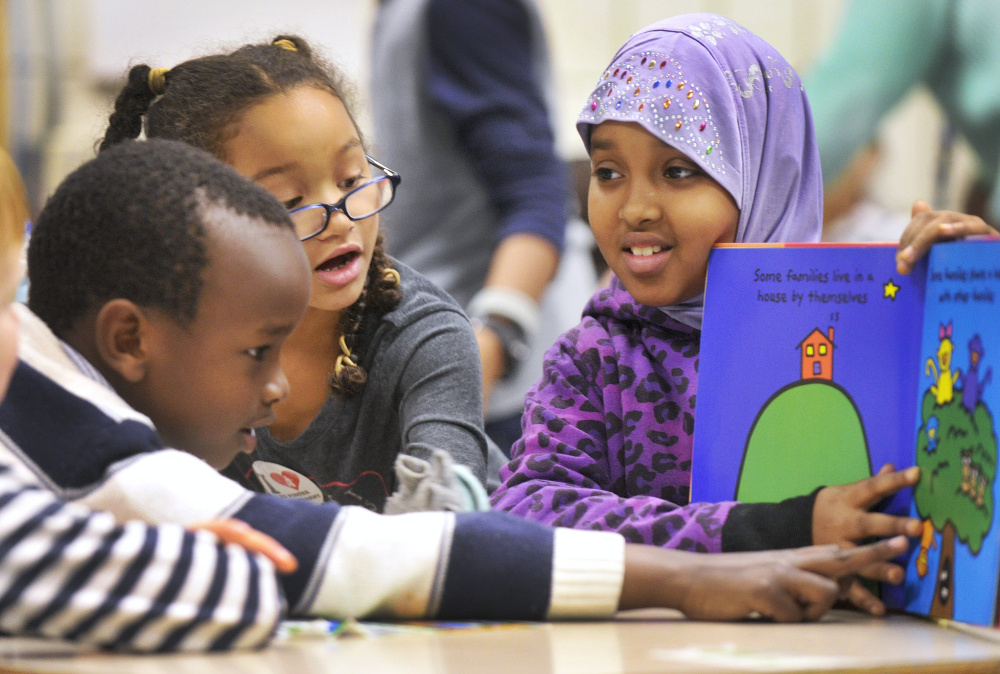Nasra Omar, 9, a civil rights team member at Portland's Riverton Elementary School, mentors first-graders Alpha Kabagambe, left, and Maya Fairclough.