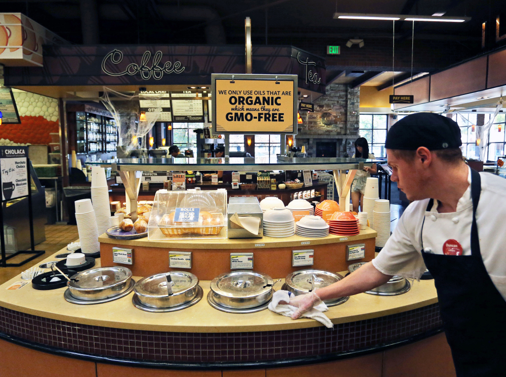 A grocery store employee in Colorado wipes down a soup bar with a sign overhead that says the soups were prepared with organic, GMO-free oils. Maine has a law that requires labeling of genetically engineered food once five contiguous states, including Maine, adopt similar laws by Jan. 1, 2018.
