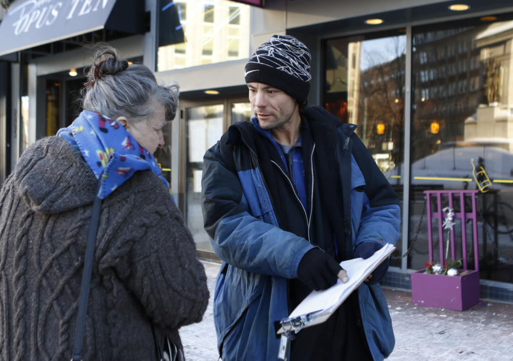 Brandon Scott, right, speaks with Joyce Lorraine, as he works to collect signatures on a petition about a casino referendum on Thursday  in Monument Square in Portland,. Joel Page/Staff Photographer