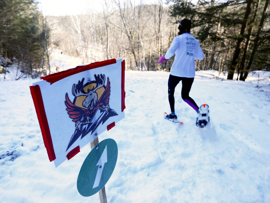 Linda Davis passes a directional sign after emerging from the trees while competing in the 5k race. Derek Davis/Staff Photographer