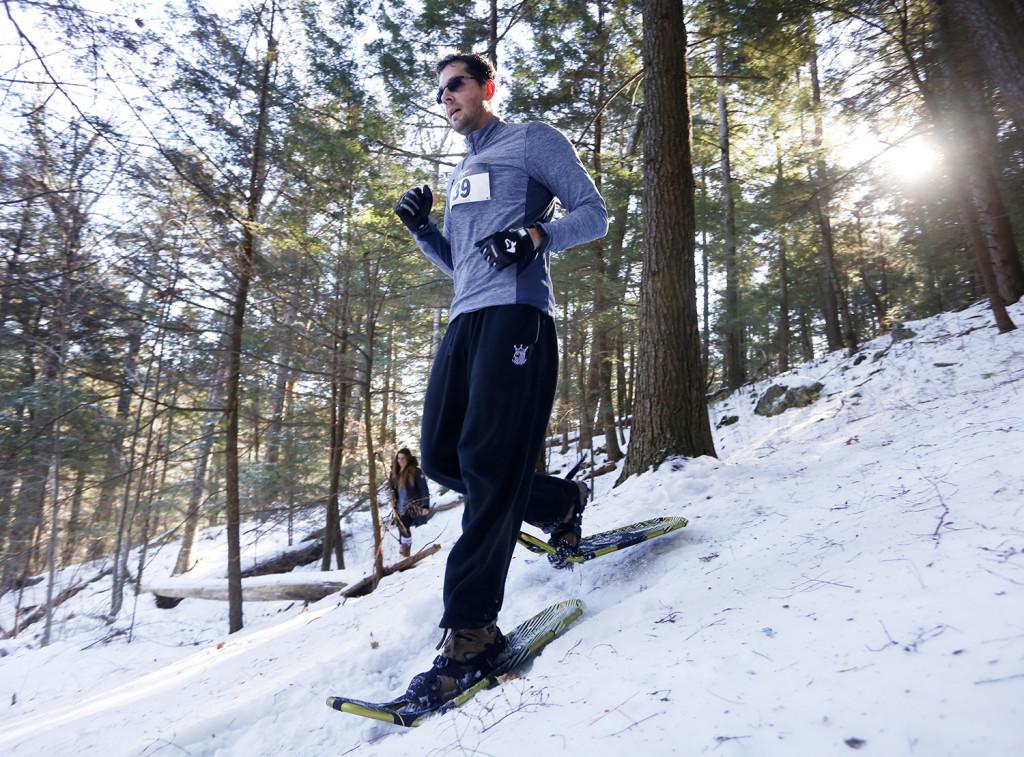 Shawn Walker traverses a trail in the woods during the 5k race. Derek Davis/Staff Photographer
