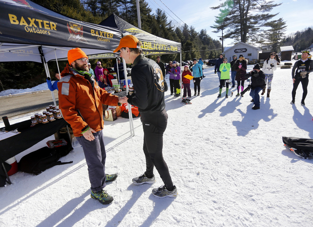 Peter Mallinowski, right, accepts his award from Adam Platz, director of Baxter Outdoors, after finishing first in his age group for the 5k race. Derek Davis/Staff Photographer