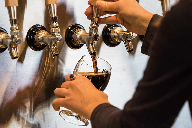 Lea Romanowsky, a tasting room ambassador at Rising Tide, pours a beer in the company's newly expanded tasting room on Fox Street.
