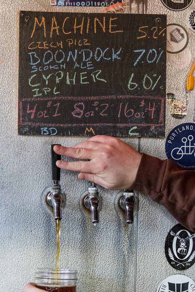 Jared McKenna, an employee at Bunker Brewing Company, pours a beer from tap in the company's all-in-one tasting room and brewery on Anderson Street in Portland.