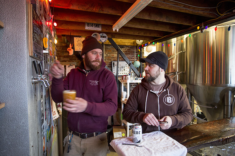 Bunker Brewing Company co-owner Chresten Sorensentalks with fellow employee Jared McKenna at the company's brewery and tasting room after pouring a pint of beer.