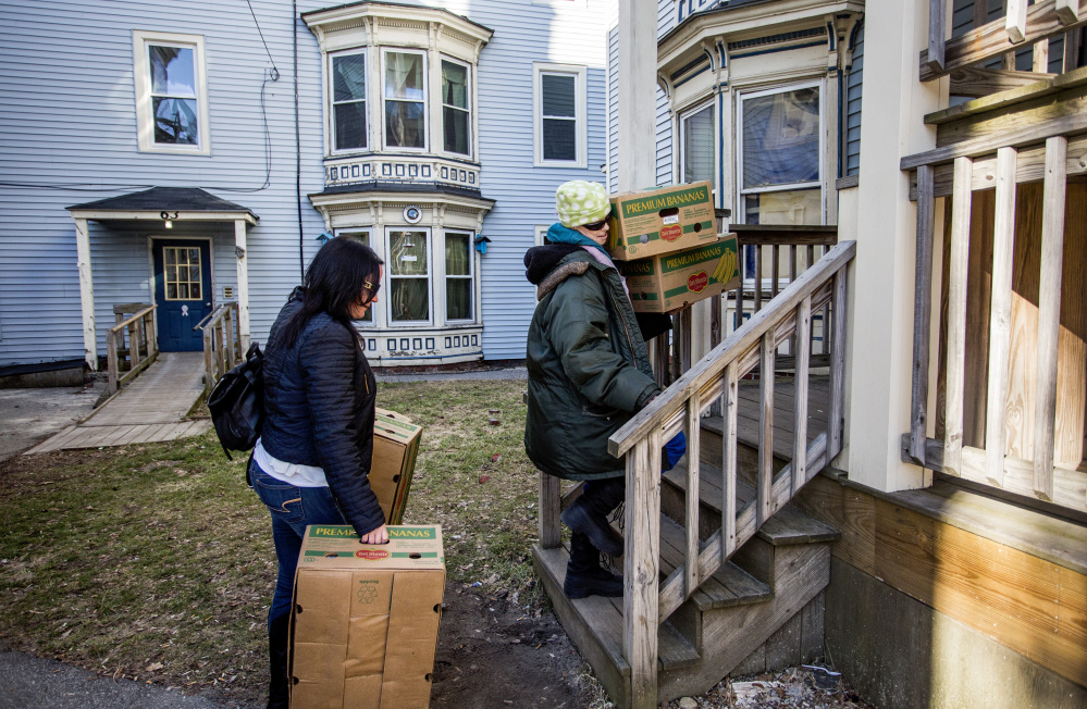 Anna Teague, right, and Chrissy Whitlock, a case manager from Shalom House, carry boxes Monday to Teague's apartment. Teague, one of numerous residents being evicted from buildings at 61-69 Grant St., said moving has been especially hard because she has cancer.