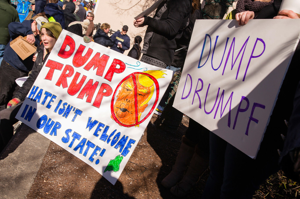 Anti-Trump protesters display signs outside the Donald Trump rally at ...