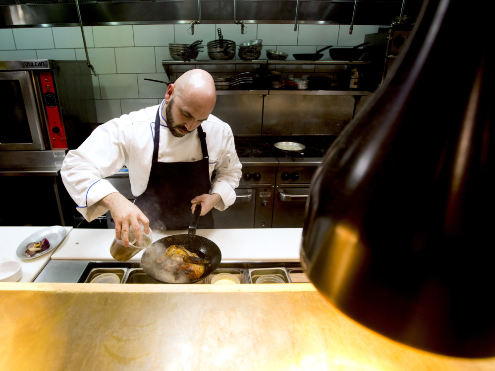 """Bo Byrne, executive chef at Tiqa, prepares Sumac Roasted Chicken, a Mediterranean dish. Before Tiqa hired him in October, Byrne says, he'd never even made hummus """"the right way."""""""