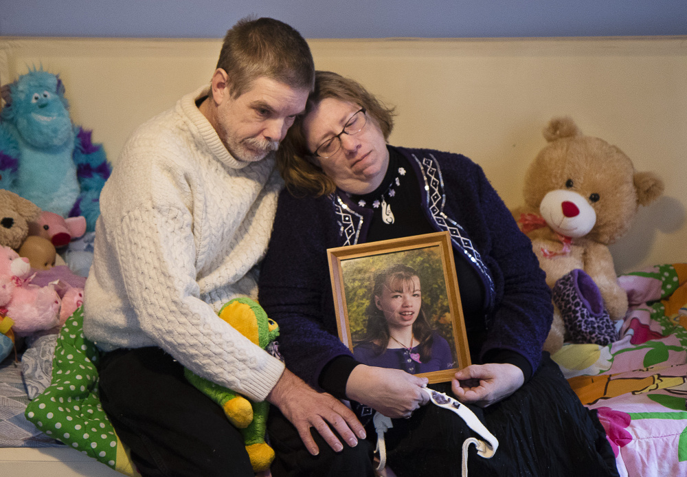 Robert and Susan Meehan sit on the bed of their daughter Cyndimae and hold her photo on Monday. Cyndimae, who moved to Maine with her family in 2013 so that her seizure condition could be legally treated with medical cannabis, died unexpectedly Sunday in her father's arms.