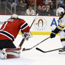 New Jersey goalie Keith Kinkaid makes a save as Boston's Loui Eriksson skates in front of the net during the Devils' 2-1 win Tuesday night.   The Associated Press
