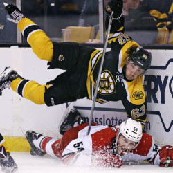 Boston Bruins left wing Brad Marchand, top, goes airborne after slamming Carolina Hurricanes defenseman Brett Pesce (54) to the ice during the second period of an NHL hockey game in Boston, Tuesday, April 5, 2016. (AP Photo/Charles Krupa)
