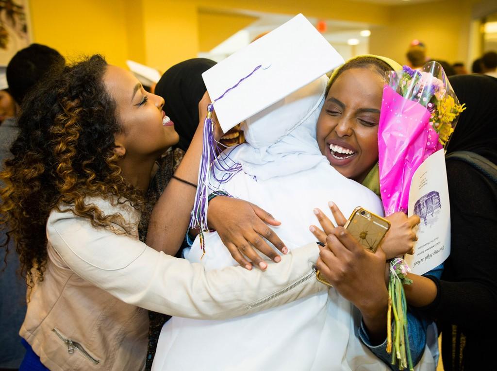 Deering High School juniors Elwaad Werah, left, and Iffrah Hassan congratulate Deqa Dahir after her graduation Thursday at the Cross Insurance Arena.