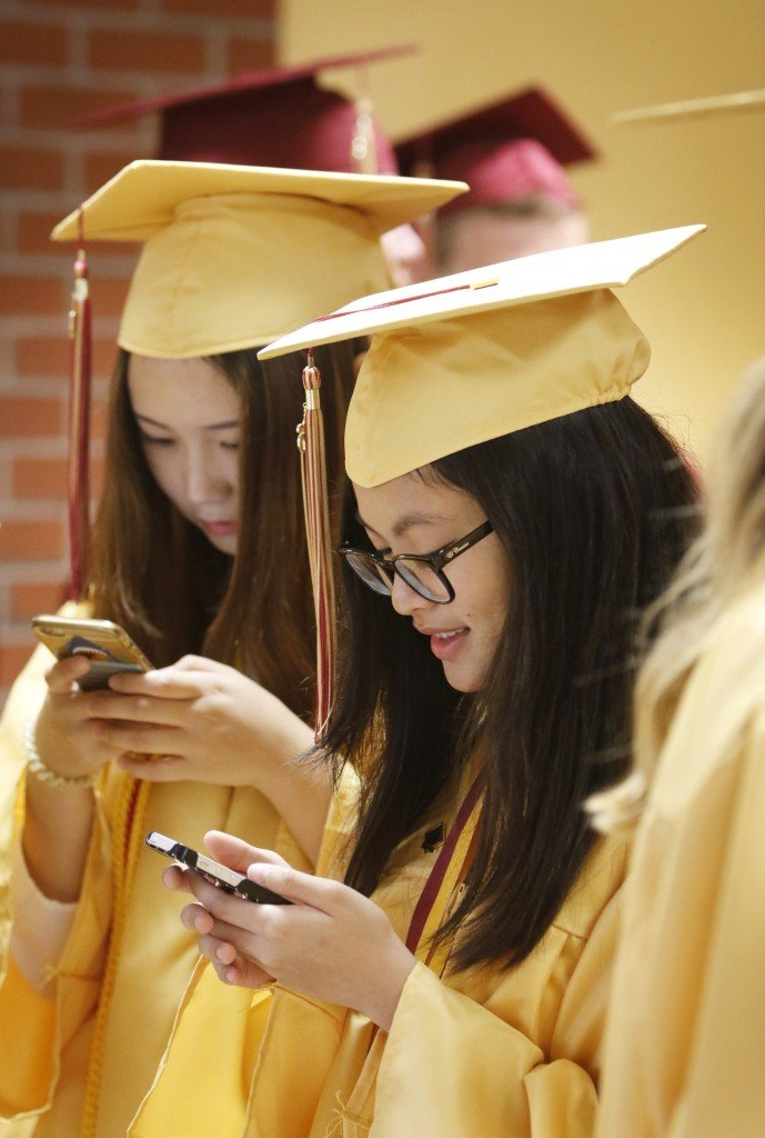 SACO, ME - JUNE 5: Minah Nguyen (cq), right, and Shannon Shou check their phones while waiting to file into the gymnasium for Thornton Academy graduation.(Photo by Jill Brady/Staff Photographer)