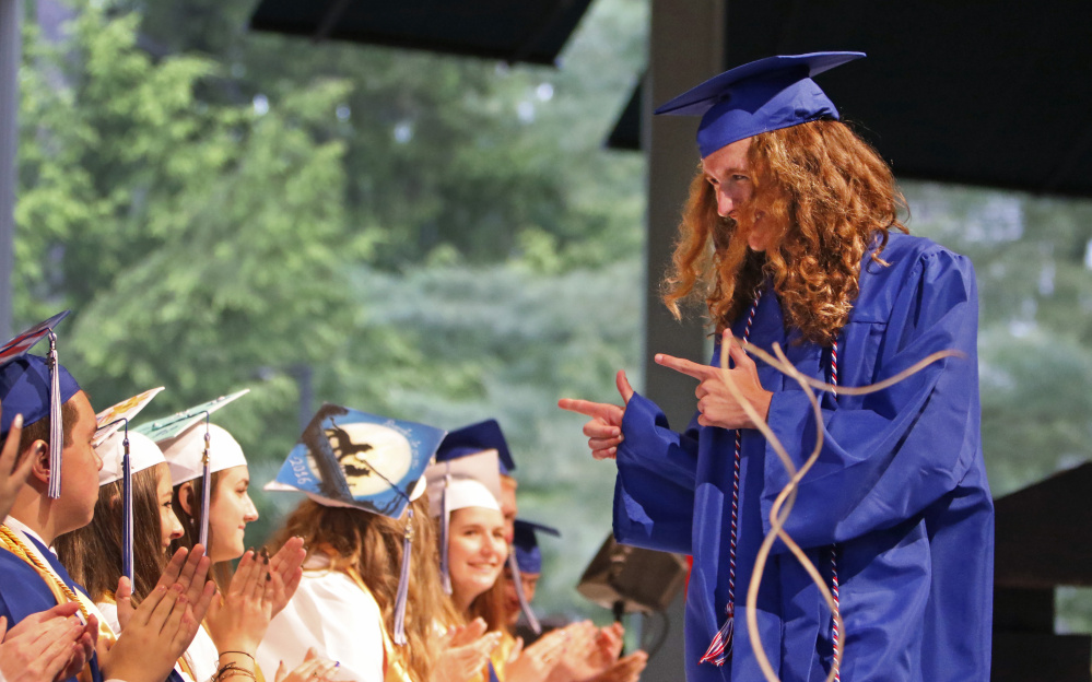 Noah Doucette points to his classmates as they applaud him on his way to receive his diploma at Old Orchard Beach High School's graduation Sunday at the Seaside Pavilion.
