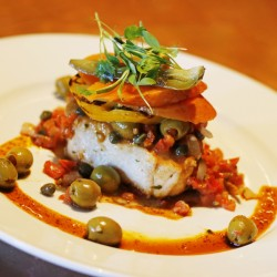 Zapoteca's Veracruzano halibut ($28) is made with green olives, capers, raisins and diced tomato, with thick slices of pickled carrots and jalapeños. Below, Diners place their orders during a busy dinner hour. The cilantro-scented guacamole, bottom, is shaped with a ring mold for serving.