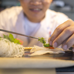 Pau Lim places scallions atop a lunch sashimi platter.