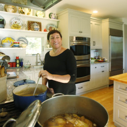"""Kathy Gunst stirs the soup in the kitchen of her South Berwick home. Her new cookbook,  """"Soup Swap,"""" below, grew out of a monthly community soup swap that she and her husband attend. """"I really don't like potlucks,"""" she says, but with the soup swap, """"you go home with more than you bring. It's a total win-win."""""""