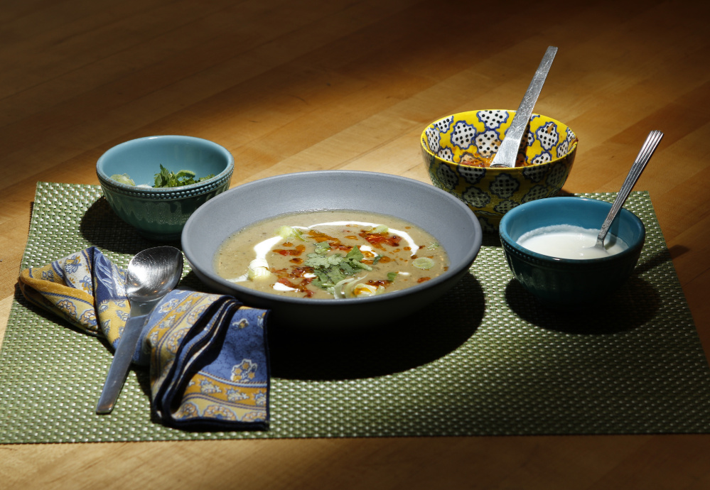 Award-winning food writer Kathy Gunst has a new cookbook which includes a recipe for this mulligatawny soup, which can be topped with, from left, cilantro and scallions, a tomato chili topping and greek yogurt. Gregory Rec/Staff Photographer