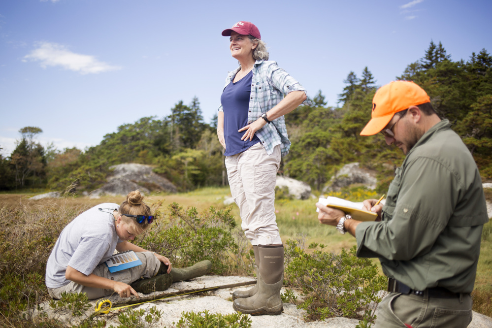 Bev Johnson, center, with her student Kelsey Chenoweth, left, and Philip Dostie, assistant instructor in environmental geochemistry, at Sprague Marsh. Brianna Soukup/Staff Photographer
