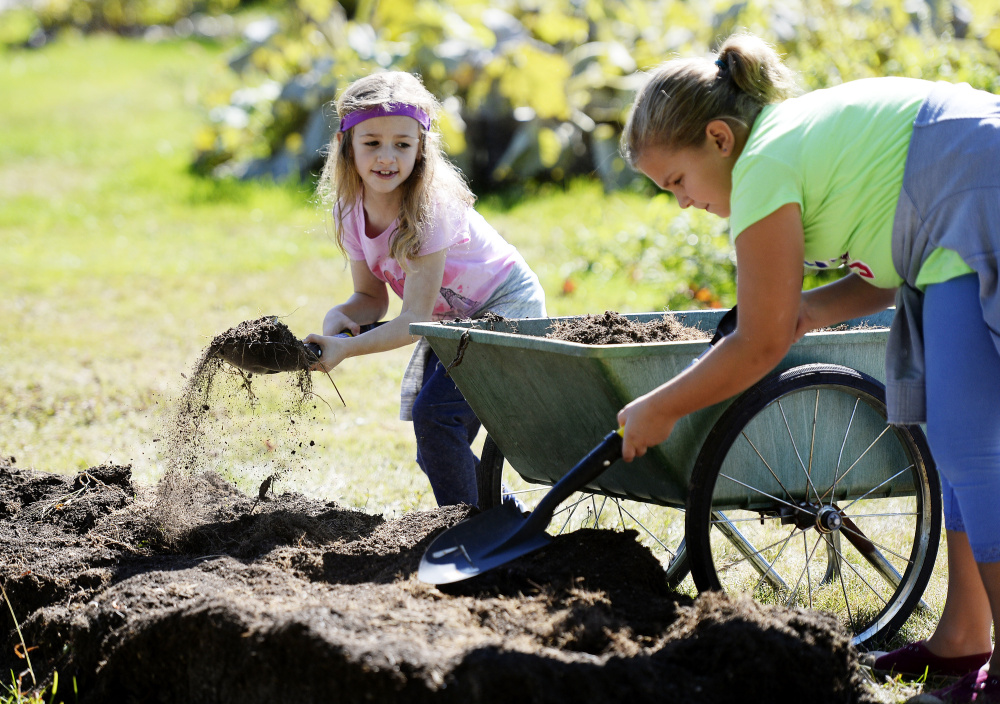 Second-grader Macie Helms and third-grader Elspeth Migliore move soil in the garden. Shawn Patrick Ouellette/Staff Photographer