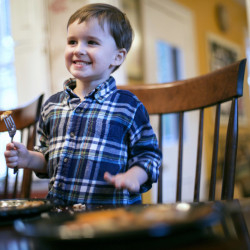 Henry, the 3-year-old son of Brunswick resident Laura Franz, is all smiles as he tastes Acadian redfish sticks he helped make with Christine Burns Rudalevige.